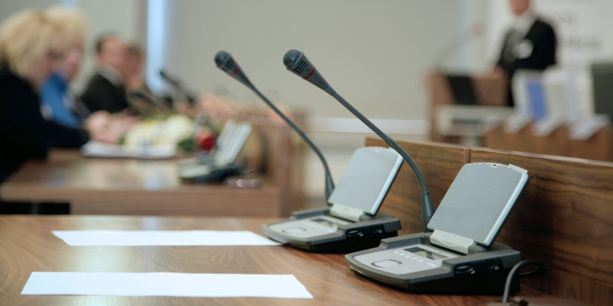 Micros en premiers-plans renvoyant à une salle d'assemblée