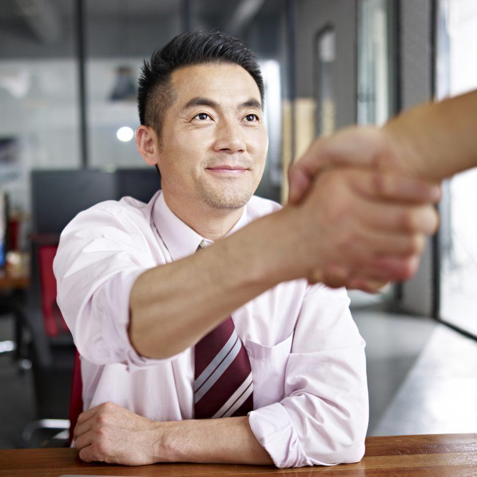 Collaborateur en premier plan serrant la main d'un de ses pairs