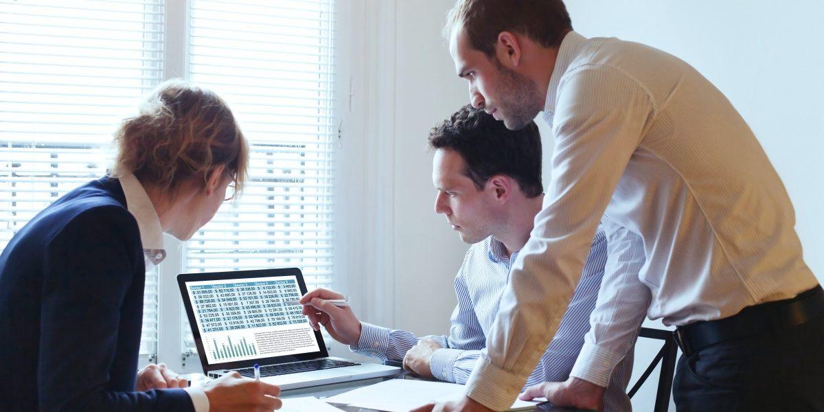 Un employé montre des chiffres clés et statistiques à deux de ses collègues