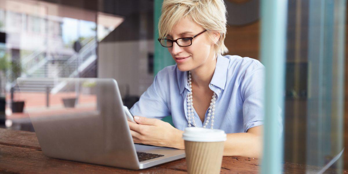 Une femme consultant l'actualité lors d'une pause café