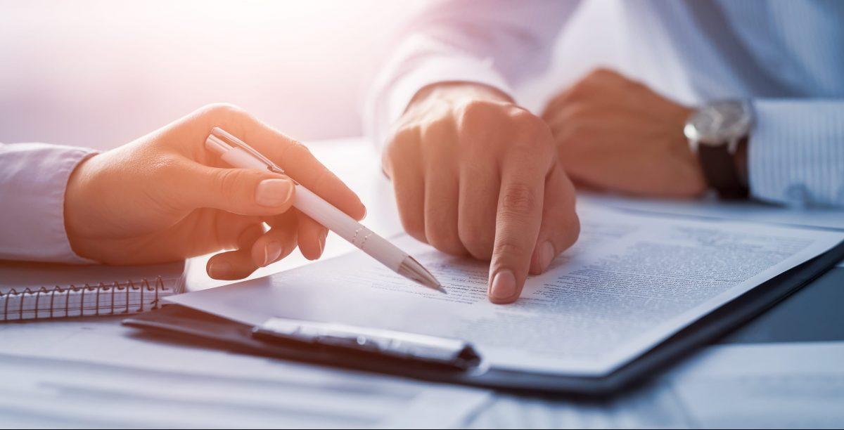 Deux personnes scrutant un document d'ordre réglementaire