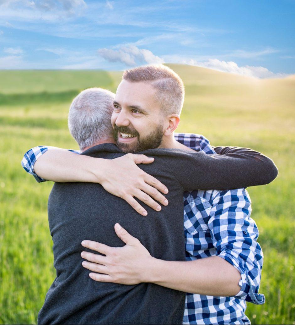 Un homme et son père dans les bras l'un de l'autre au milieu d'une plaine