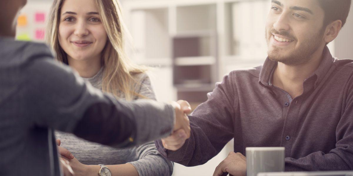Deux employés recevant un candidat lors d'un entretien d'embauche (poignée de main entre le candidat et un des employés)