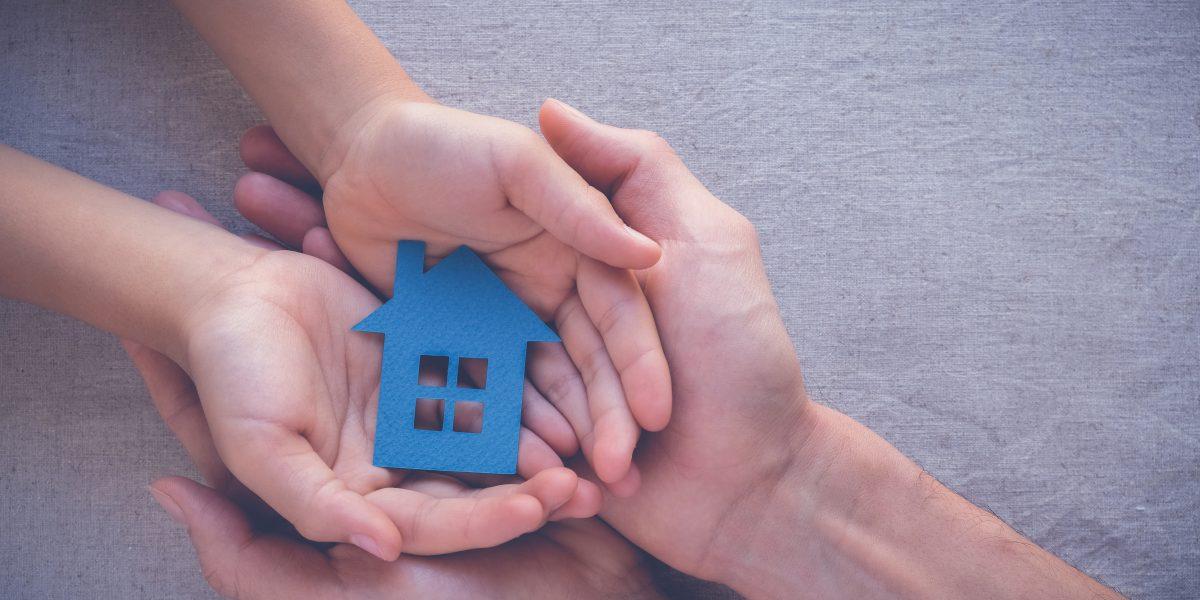 Deux pairs de mains superposés soutenant une maison miniature