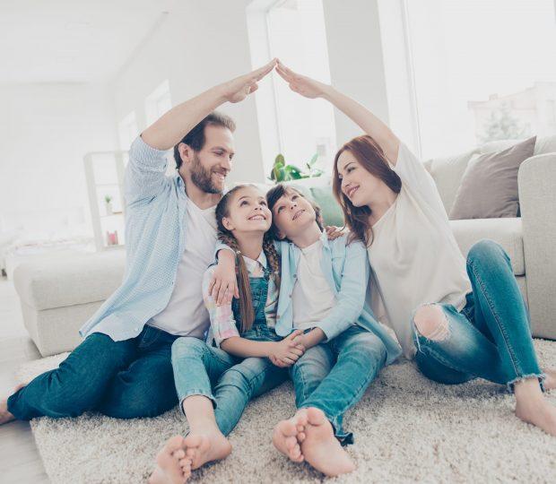 Des parents protégeant symboliquement leurs enfant en formant le toit d'une maison avec leur maison au milieu de leur salon