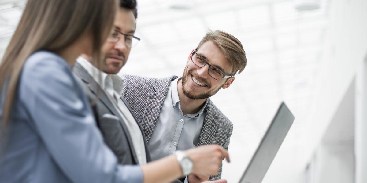 Trois personnes debout discutant d'un sujet et pointant du doigt l'ordinateur