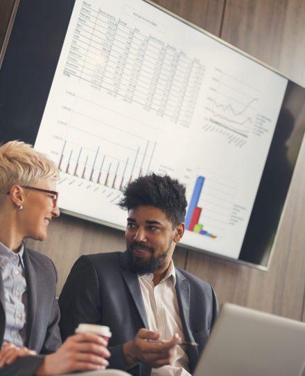 Deux collègues discutant, dos à un écran montrant des statistiques de performance