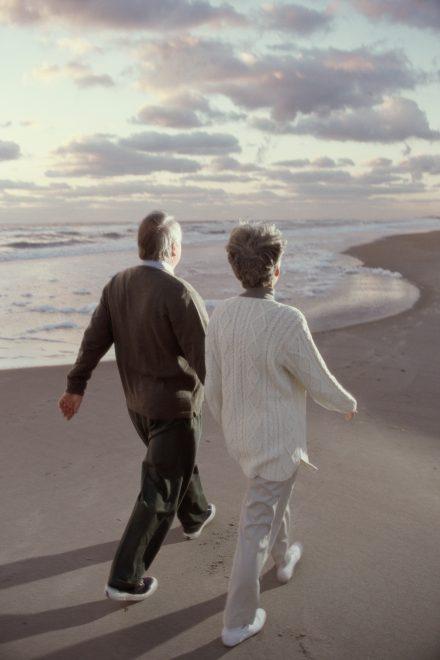 Un couple de personnes âgées marchant sur la page au bord de l'eau