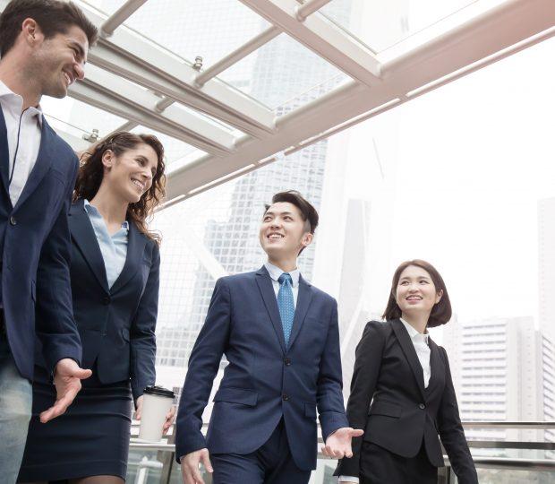 Quatre personnes en discussion dans un couloir sur leur lieu de travail