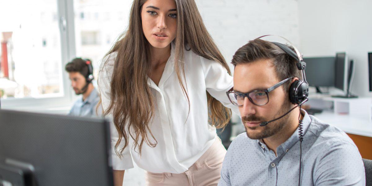 Responsable aidant et contrôlant un employé devant son ordinateur et avec son casque