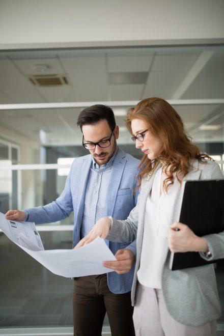 Deux personnes pointant du doigt et regardant un document